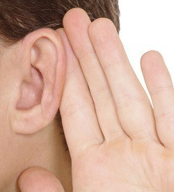 Person holds hand near ear and listening to something