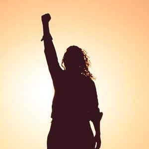 silhouette of woman with fist raised in power