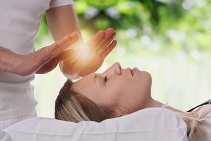 Woman having reiki healing treatment