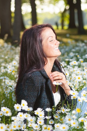 Beutiful smiling happy woman on field of flowers